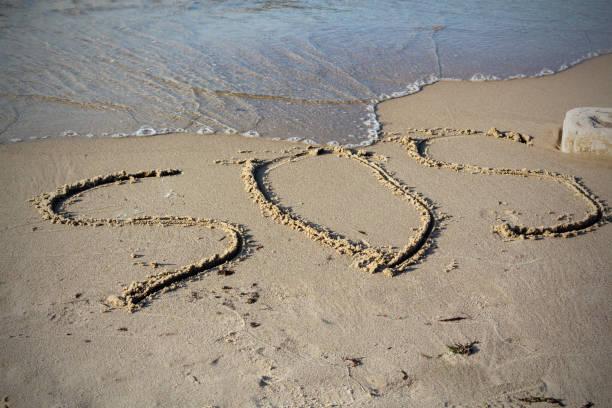 sos - wort auf dem sandstrand mit der weichen welle gezeichnet - rettungsinsel stock-fotos und bilder
