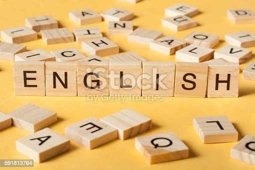 Word english made with block wood letters next to a pile of other letter over wooden table.