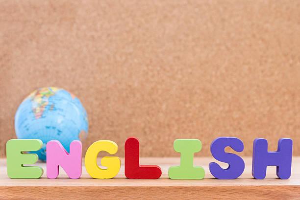 word english with globe over wooden background - sprüche englisch stock-fotos und bilder