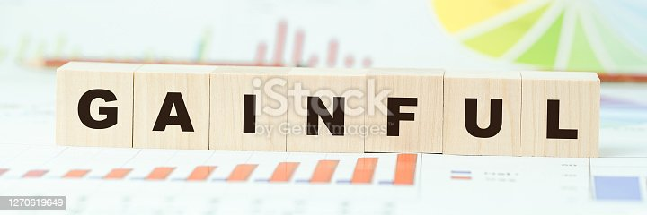 word gainful made with wooden blocks on desk with different color graphs and diagram in light room closeup