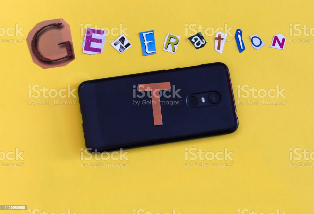 Word 'Generation T' formed with cut letters and a smarthphone. The new generation of technology after Millennial also called Alpha Generation. stock photo