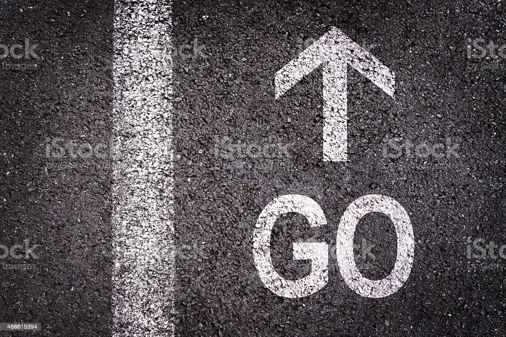 Word go and an arrow written on  asphalt stock photo