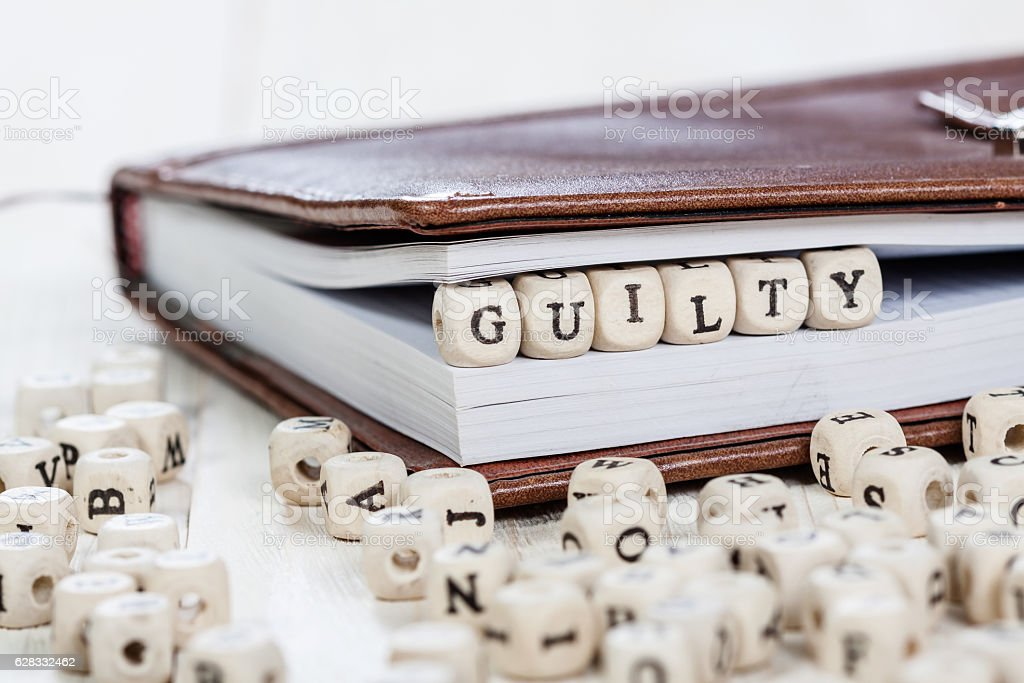 Word GUILTY on old wooden table. stock photo