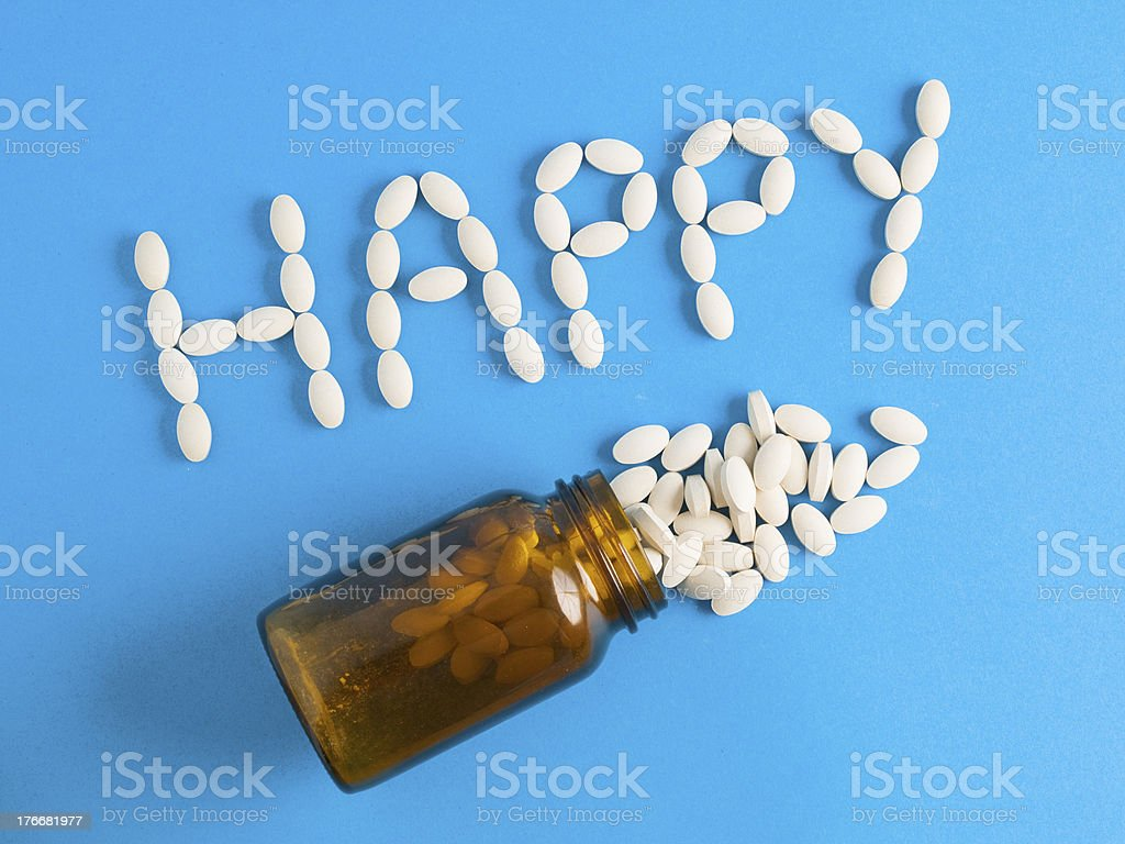 Word 'happy' written whith pills on blue background royalty-free stock photo