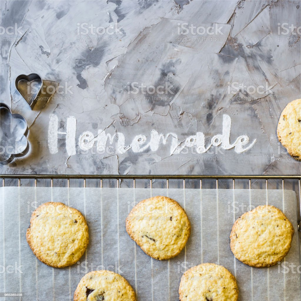 Word Homemade is written on a gray concrete background of flour. Next to the baking tray with cookies. Homemade pastry concept. Top view, flat lay royalty-free stock photo
