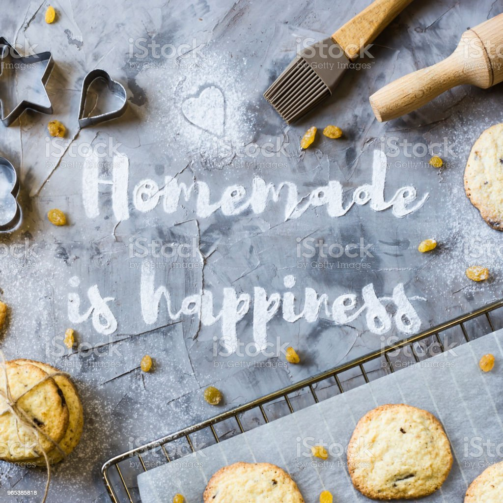 Word Homemade is written on a gray concrete background of flour. Next to the baking sheet with biscuits, shapes and rolling-pin. Homemade pastry concept. Top view, flat lay zbiór zdjęć royalty-free