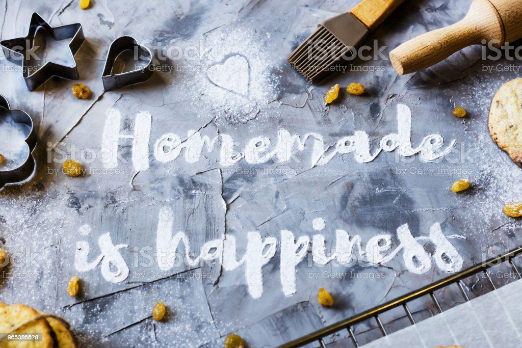 字自製是寫在灰色的具體背景麵粉。旁邊的烘烤板餅乾, 形狀和滾動針。自製糕點的概念。頂部視圖, 平躺 - 免版稅仿舊圖庫照片