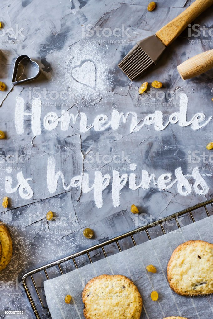 Word Homemade is written on a gray concrete background of flour. Next to the baking sheet with biscuits, shapes and rolling-pin. Homemade pastry concept. Top view, flat lay royalty-free stock photo