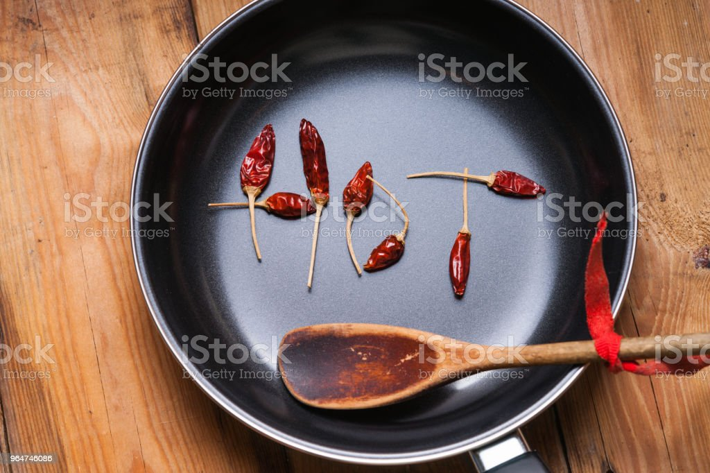 Word HOT made from dried chili peppers on a frying pan and wooden spoon royalty-free stock photo