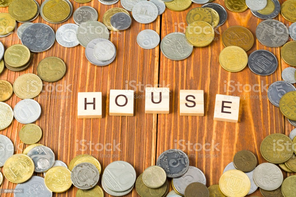 Word HOUSE on wooden cube with coins frame at wood background. Savings plans for housing financial concept stock photo