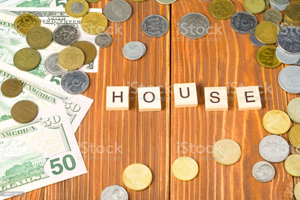 Word HOUSE on wooden cube with money frame at wood background. Financial concept stock photo