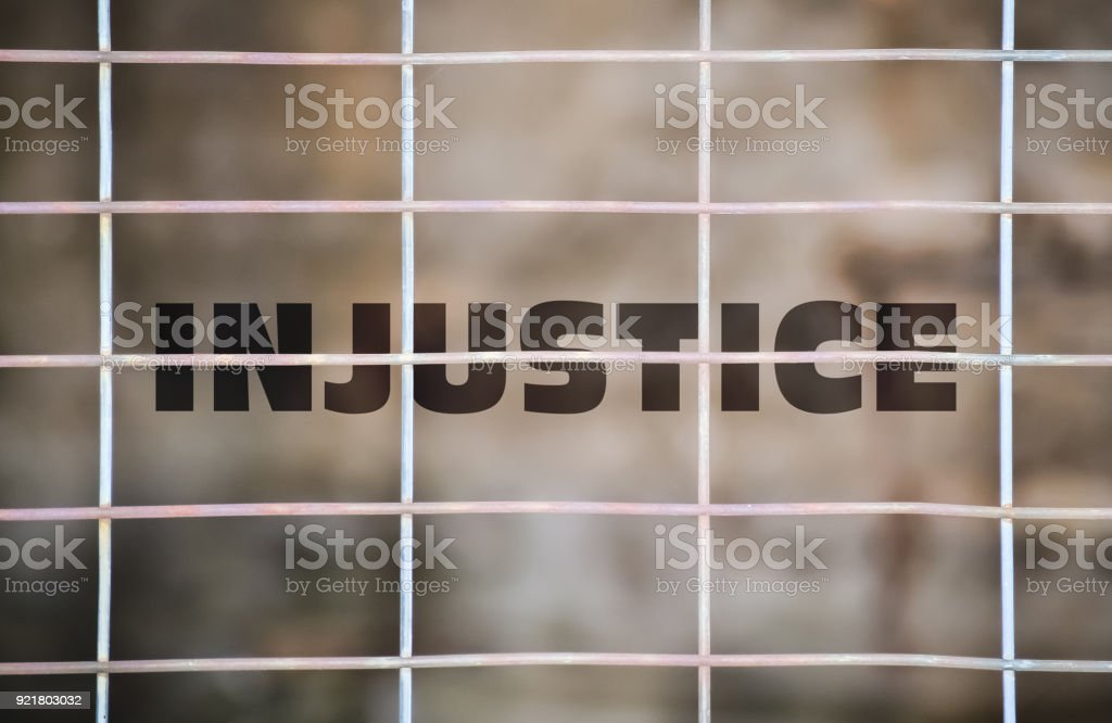 Word Injustice under a wire fence stock photo