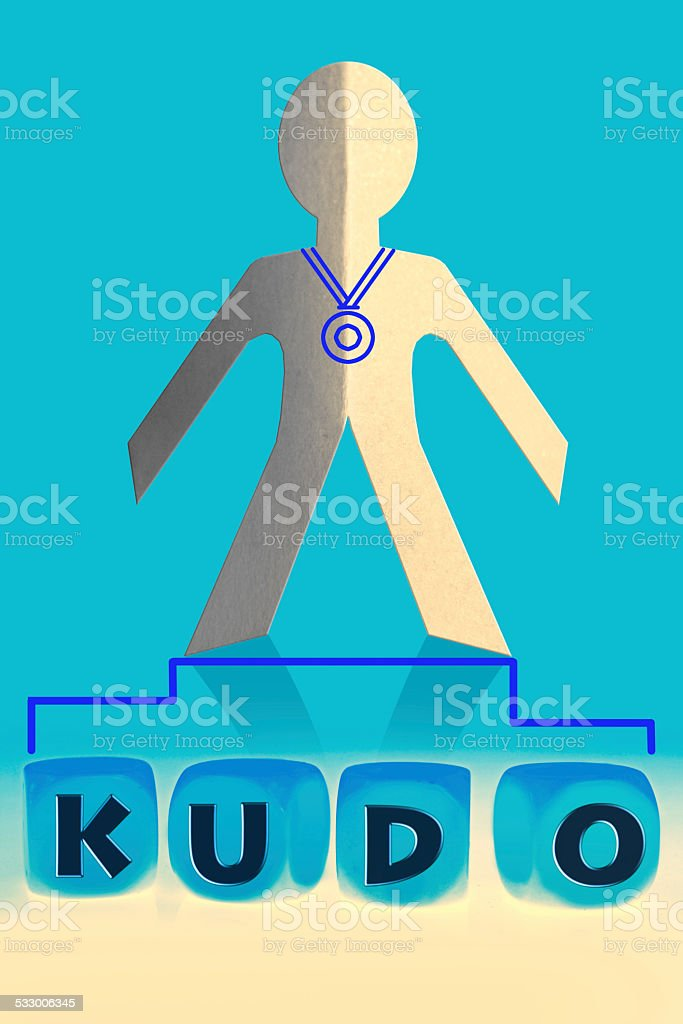 word Kudo on cubes in front of paper man stock photo