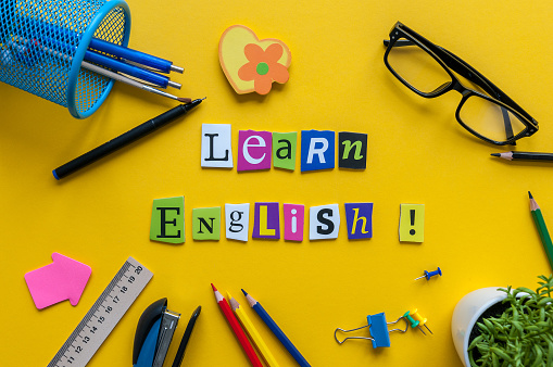 Word LEARN ENGLISH made with carved letters onyellow desk with office or school supplies, stationery. Concept of English language courses.