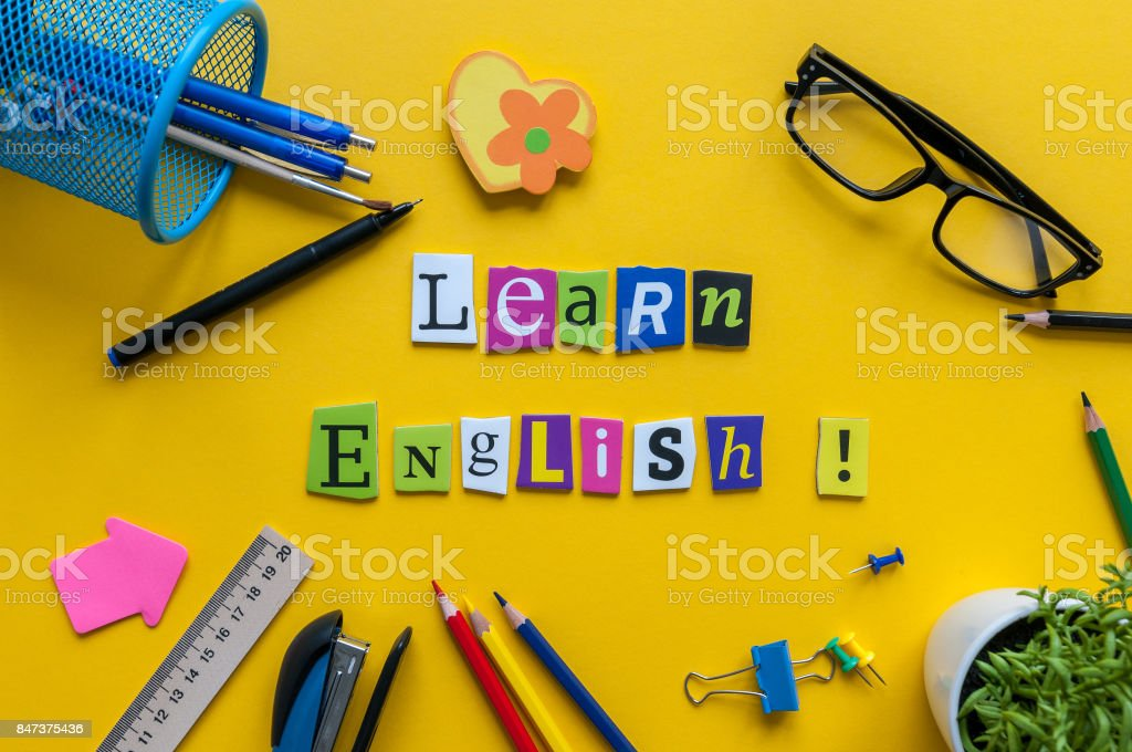 Word LEARN ENGLISH made with carved letters onyellow desk with office or school supplies, stationery. Concept of English language courses stock photo