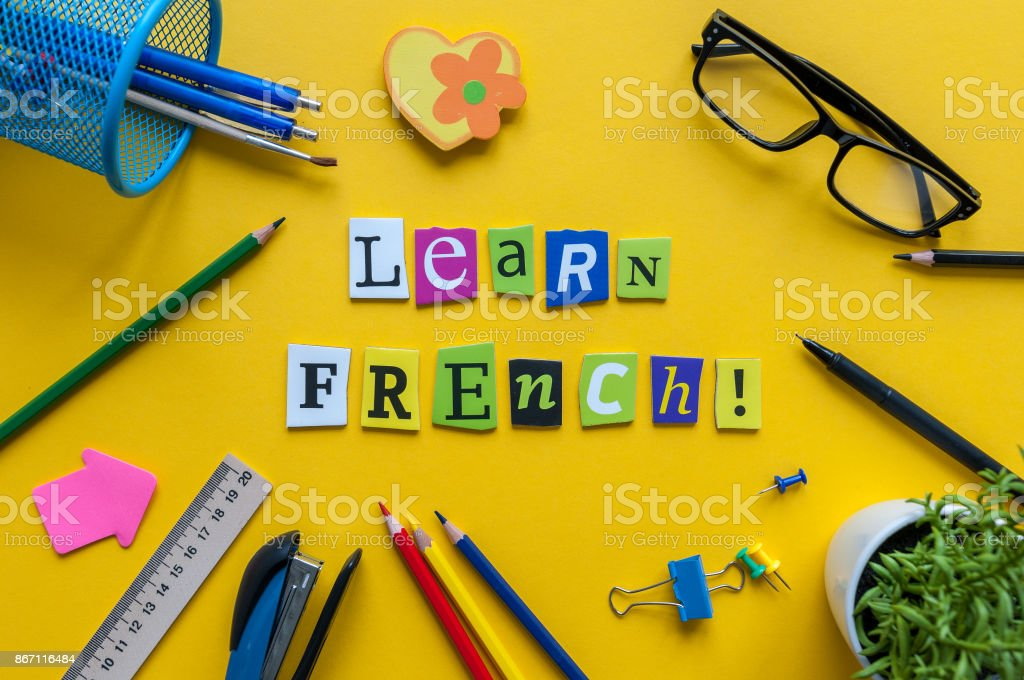 Word LEARN FRENCH made with carved letters on yellow desk with office or school supplies, stationery. Concept of Franch language courses stock photo