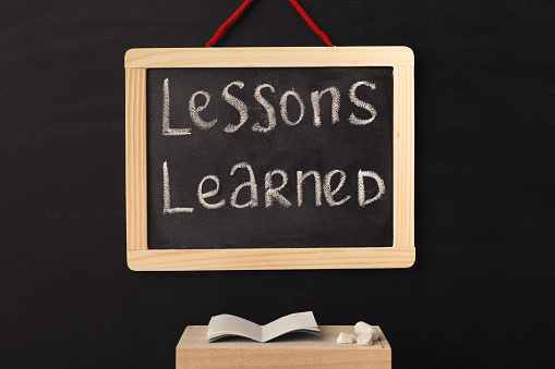 Word lessons learned written on miniature chalkboard in classroom against black background. Back to school concept. Educational background.