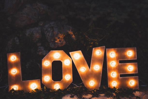 wort-liebe, bestehend aus den buchstaben hervorgehoben mit lampen stehend auf rasen in der nacht - schöne englische wörter stock-fotos und bilder
