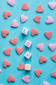 istock Word Love Constructed from Stacked Letter Cubes. Pink Red Sugar Candy Sprinkles Scattered on Light Blue Background. Romance Valentine Charity Concept. Greeting Card Poster Banner Template 902866858