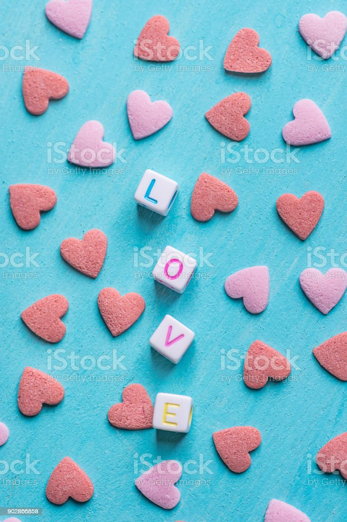 Word Love Constructed from Stacked Letter Cubes. Pink Red Sugar Candy Sprinkles Scattered on Light Blue Background. Romance Valentine Charity Concept. Greeting Card Poster Banner Template stock photo