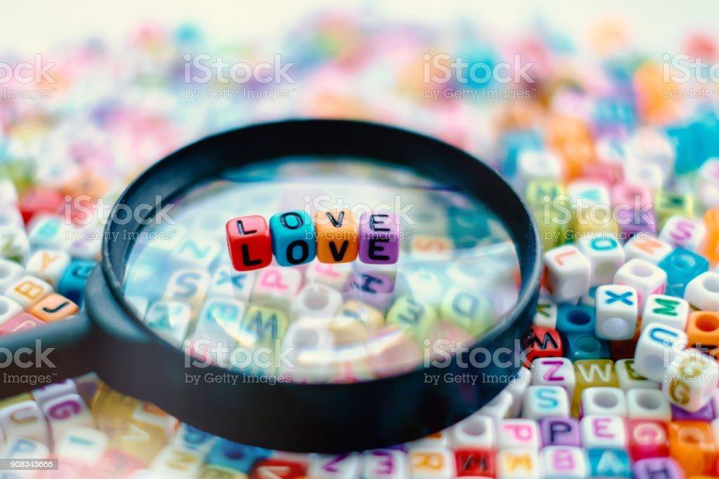 Palavra amor na lupa com fundo de grânulos de letra de alfabeto - foto de acervo