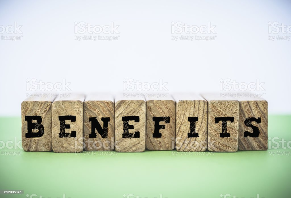 BENEFITS word made from building blocks on green and white background. Business achievement concept. stock photo