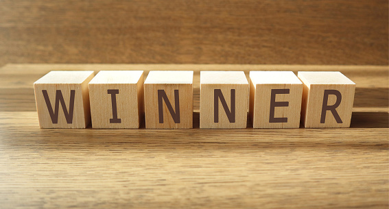 WINNER word made of wooden cubes on a brown background, business concept. Banner.