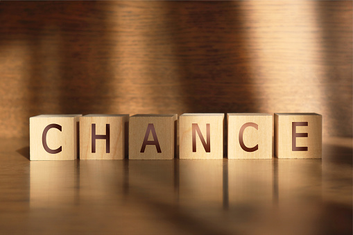 CHANCE word made of wooden cubes on a brown background, business concept.