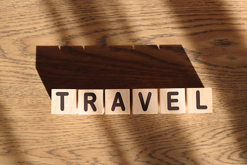 TRAVEL word made of wooden cubes on a brown background, travel concept.