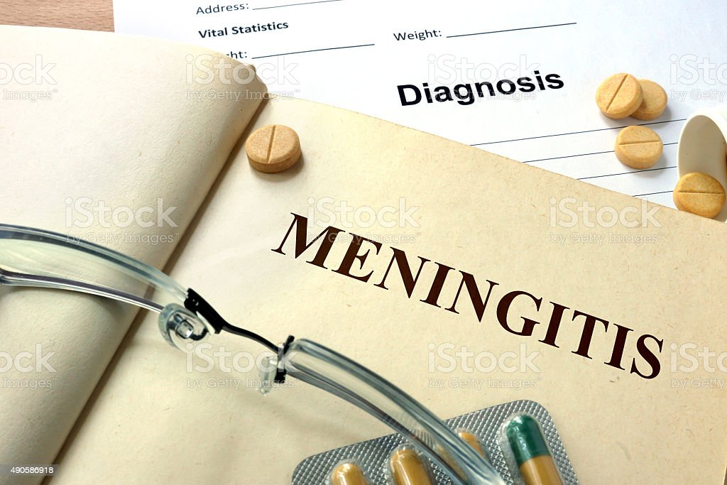 Word Meningitis  on a book and pills. stock photo