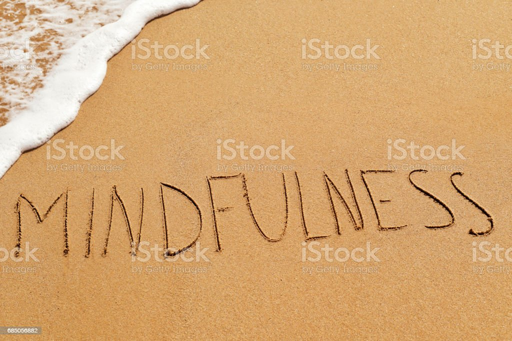 word mindfulness in the sand stock photo