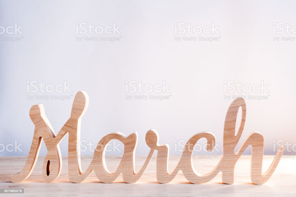 Word month of MARCH carved in wood with light background. Beginning of springtime. Spring hello concept stock photo