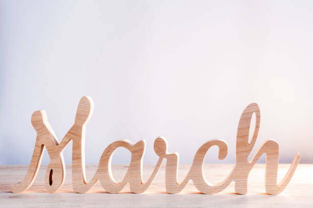 word month of march carved in wood with light background. beginning of springtime. spring hello concept - marzo foto e immagini stock