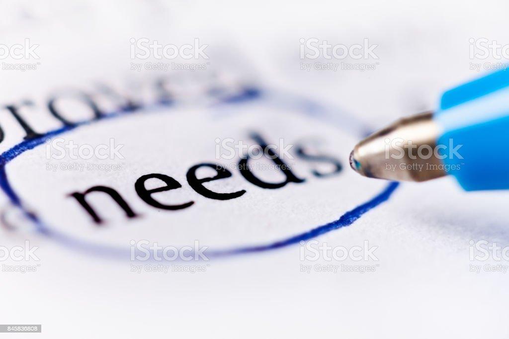 Mot «besoins» encerclé dans le stylo sur le document - Photo