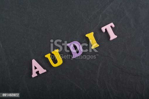istock AUDIT word on black board background composed from colorful abc alphabet block wooden letters, copy space for ad text. Learning english concept 691463922