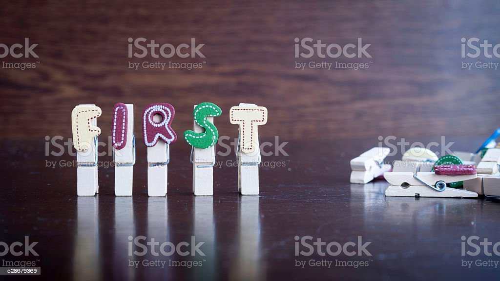 FIRST word on clothes peg stick Common business terms - Slightly defocused and close-up of TFIRST word on clothes peg stick with lots of clothes peg at background Alphabet Stock Photo