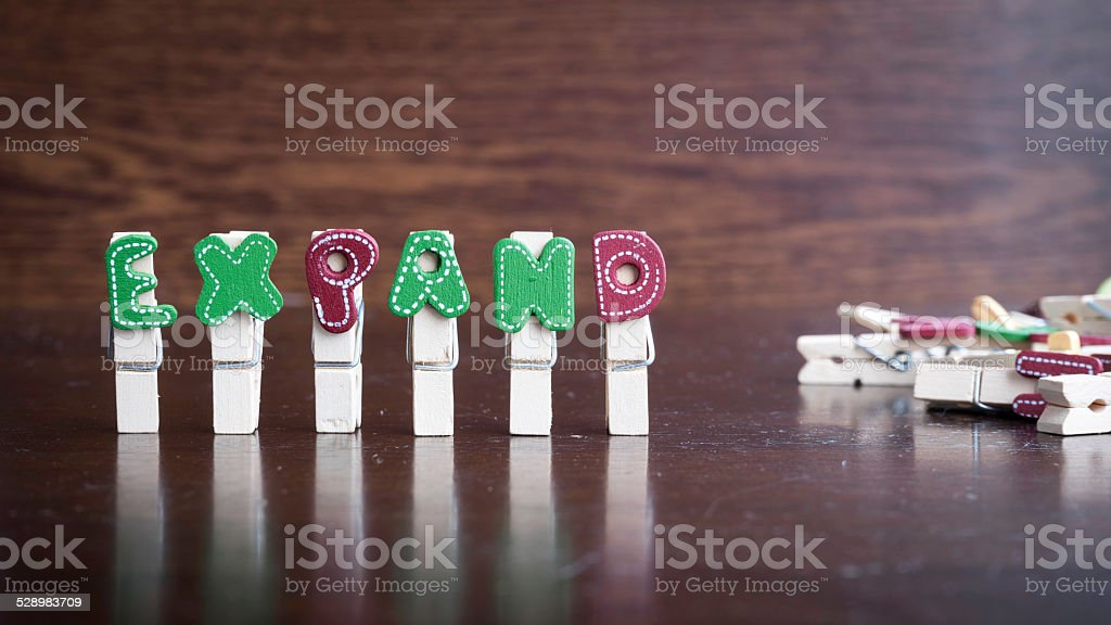 EXPAND word on clothes peg stick Common business terms - Slightly defocused and close-up of EXPAND word on clothes peg stick with lots of clothes peg at background Adulation Stock Photo