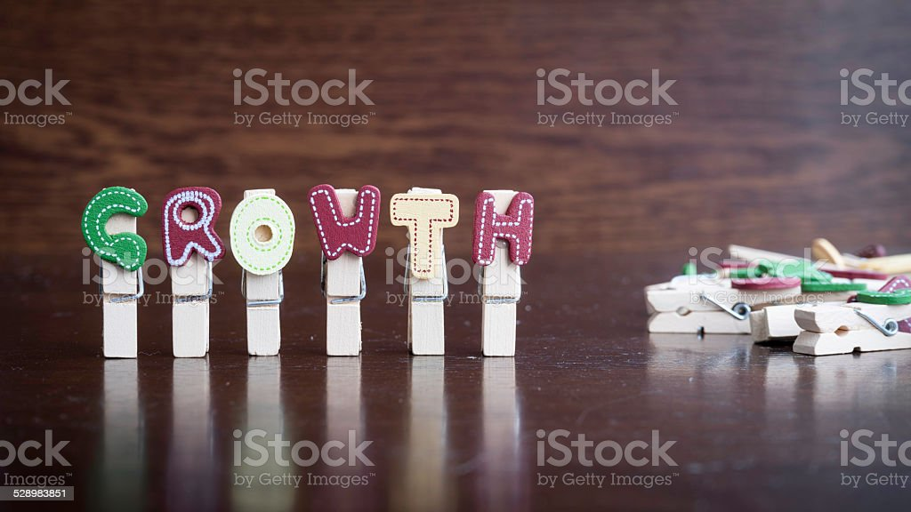 GROWTH word on clothes peg stick Common business terms - Slightly defocused and close-up of GROWTH word on clothes peg stick with lots of clothes peg at background Adulation Stock Photo