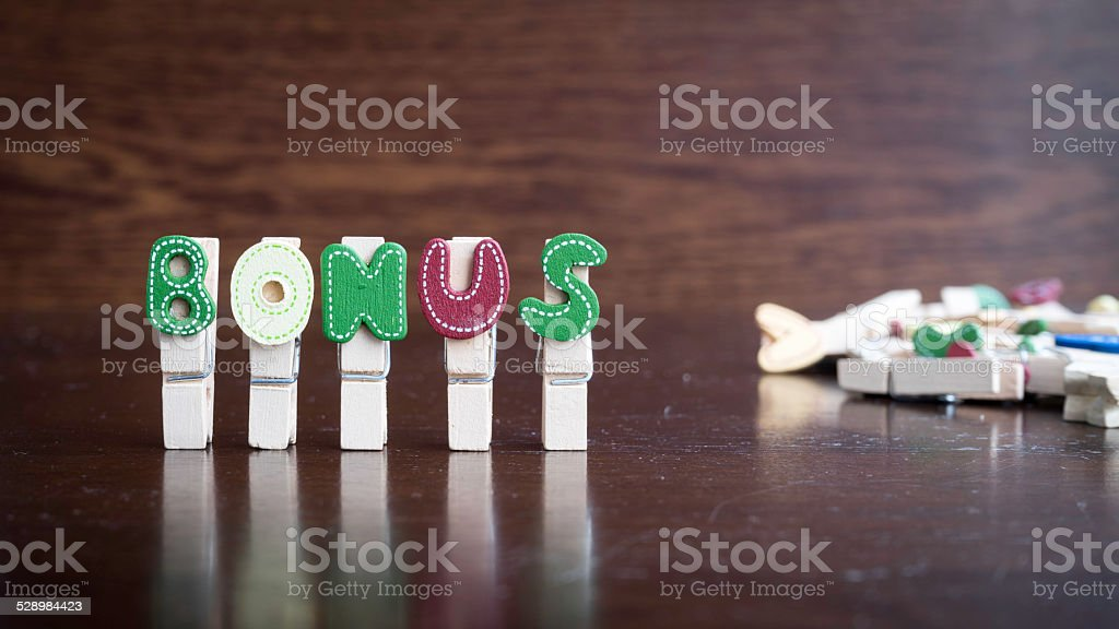 BONUS word on clothes peg stick stock photo