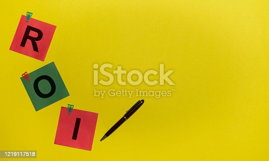 istock ROI word on green and red stickers with clips and pen on yellow background with copy space 1219117518