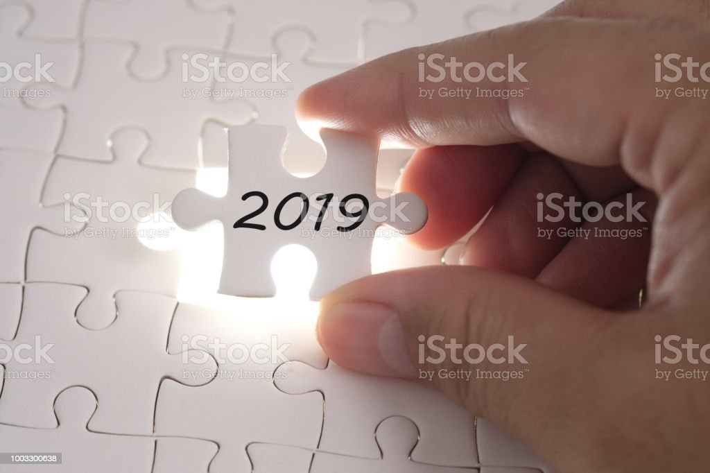 2019 word on jigsaw puzzle. Businessman hands holding white puzzle business concept. Business, finance, salary, crisis, and development concept. New year planing. stock photo