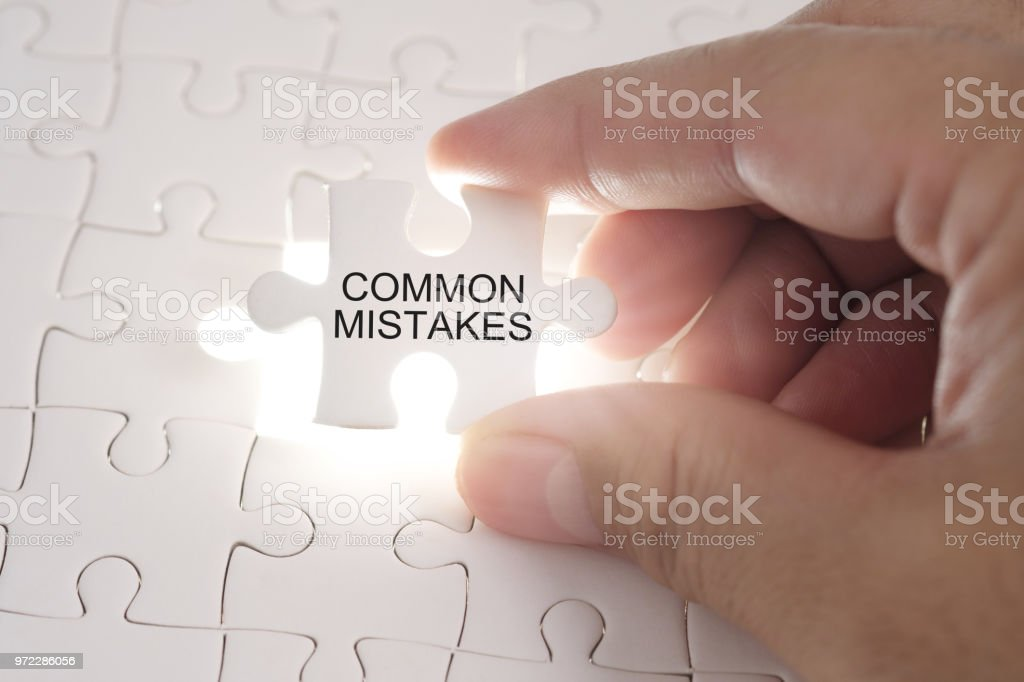 COMMON MISTAKES word on jigsaw puzzle. Businessman hands holding white puzzle business concept. stock photo