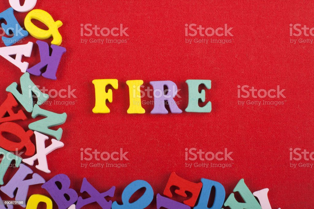 FIRE word on red background composed from colorful abc alphabet block wooden letters, copy space for ad text. Learning english concept stock photo