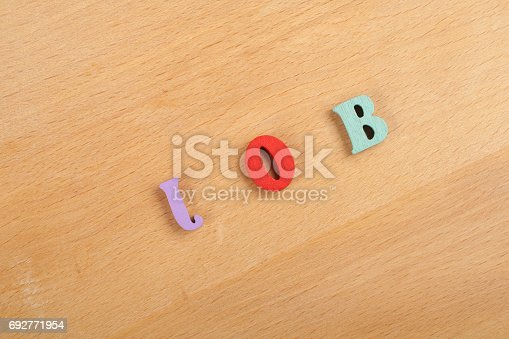 istock JOB word on wooden background composed from colorful abc alphabet block wooden letters, copy space for ad text. Learning english concept 692771954