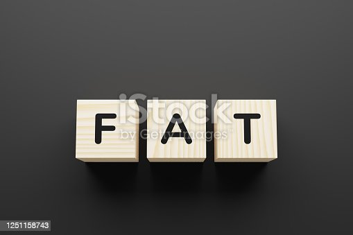FAT word on wooden blocks on gray background.