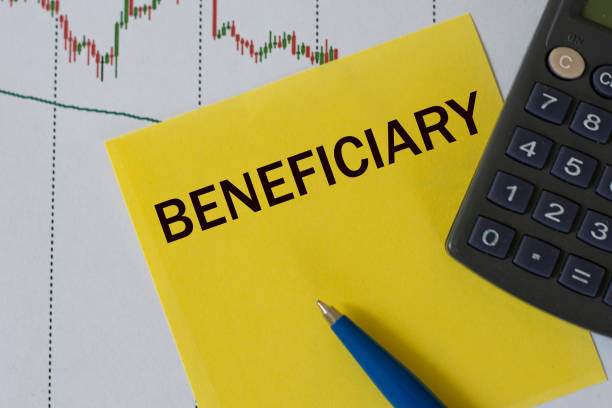 beneficiary word on yellow sheet on table with pen, calculator and graph - beneficiary stock pictures, royalty-free photos & images
