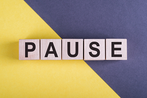 Word PAUSE on wooden cubes on yellow - gray background.