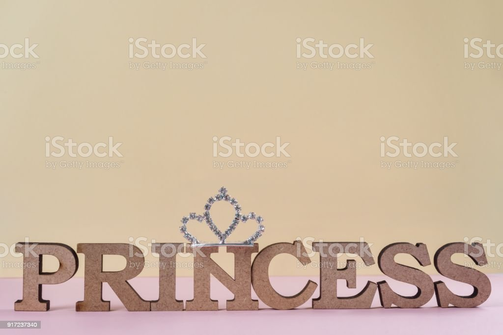 Word Princess abstract wooden letters. Pink background with sparkling crown. Textures, backgrounds, copy space stock photo