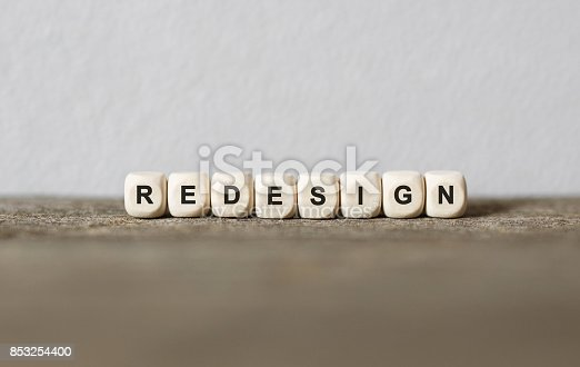 istock Word REDESIGN made with wood building blocks 853254400