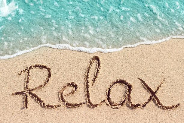 Word Relax handwritten on sandy beach stock photo